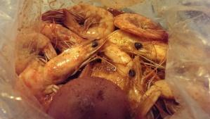 shrimps with juicy cajun seasoning with corn and potatoes